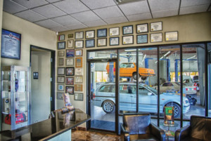 Glass wall in waiting room affords a view into the shop for a customer, enabling the customer to see what's happening with his or her vehicle.