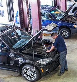 Sean Greene performs diagnostic checks on a BMW.