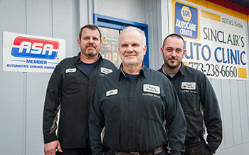 Sinclair, center (shown with his brother, Pat, left, and other employee Anthony Douglas), proudly displays his Automotive Service Association sign on the outside of his shop.