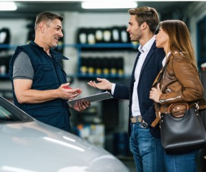 Young Happy Couple Talking To Car Mechanic In Auto Repair Shop Picture Id1191779828