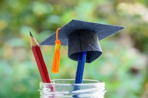 Black Graduation Cap Or A Mortarboard, Blue And Red Pencils In A Bottle
