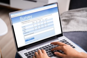 Woman Looking At Online Survey Laptop Computer